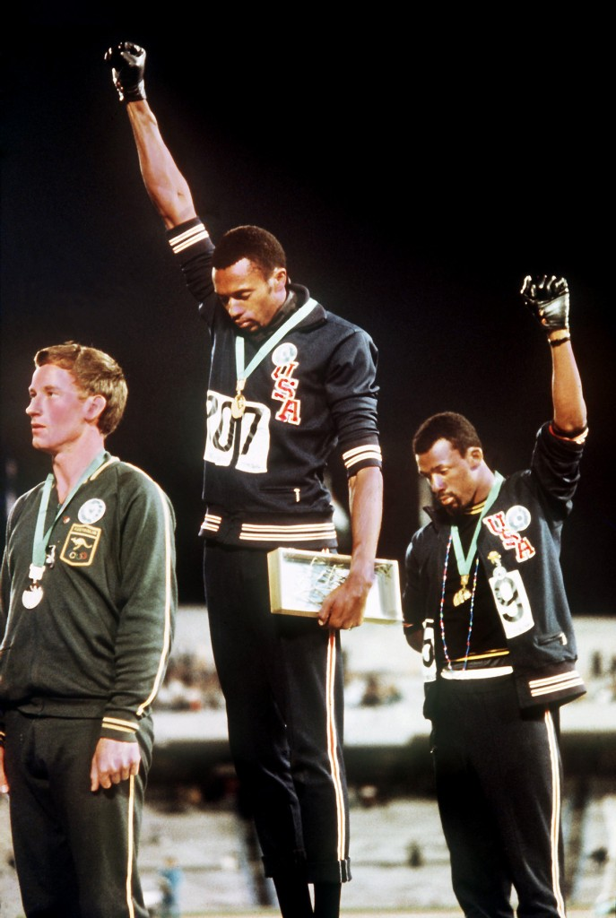 Tommie Smith (center) and John Carlos (right) on the podium after the 200 meter race at the 1960 Summer Games in Mexico City. Peter Norman took silver and is the person on the left. All three wore the OPHR button and went barefoot in protest.